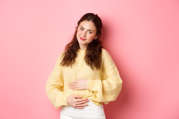 젊은 웃는 여자 임신, 그녀의 배꼽을 문지르고 카메라에 희망 행복한 얼굴로 찾고, 아기를 기대하고, 분홍색 벽에 서
