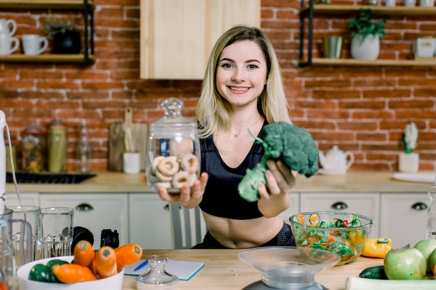 Young smiling woman in black sport clothes watching at camera and choosing between broccoli or junk food, bagels. healthy clean detox eating concept. vegetarian, vegan, raw concept. copy space.