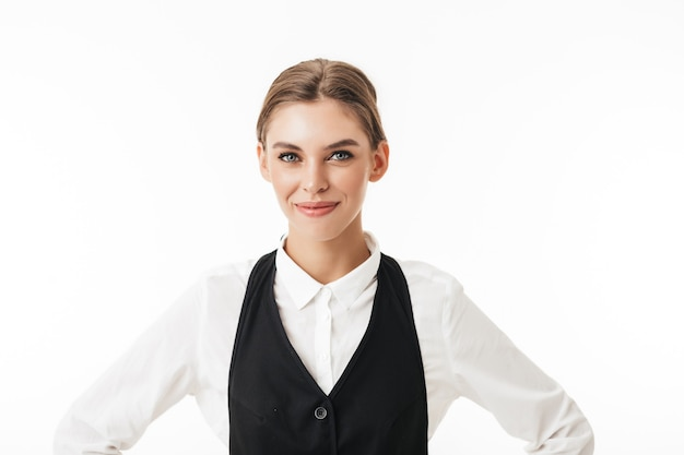 Young smiling woman in black vest and white shirt dreamily