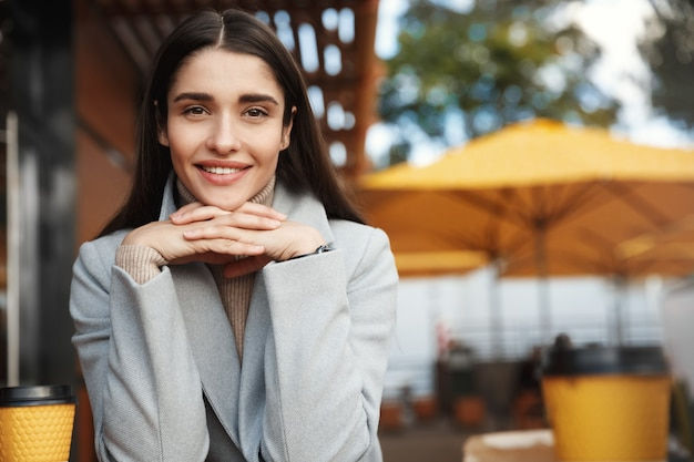Young smiling woman in a cafe, drinking coffee on a date, looking at camera.