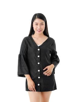 白い壁に分離された正面を見て黒のドレスで若い笑顔の女性のカジュアルなスタイル