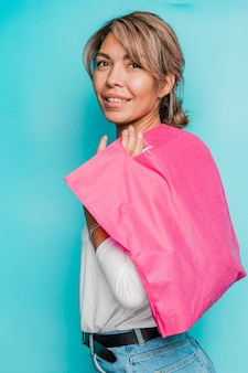 Young smiling woman in casualwear holding bright pink textile bag on shoulder