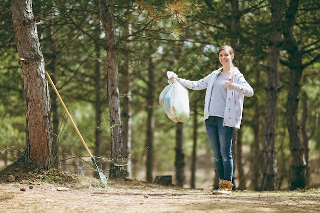 Молодая улыбающаяся женщина убирает мусор, держа мешки для мусора и показывает палец вверх в парке на зеленой стене