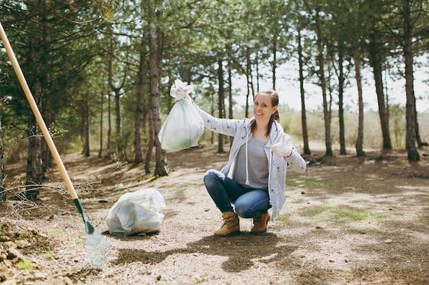 Молодая улыбающаяся женщина убирает мусор, держа мешки для мусора, показывая большой палец вверх в парке или лесу