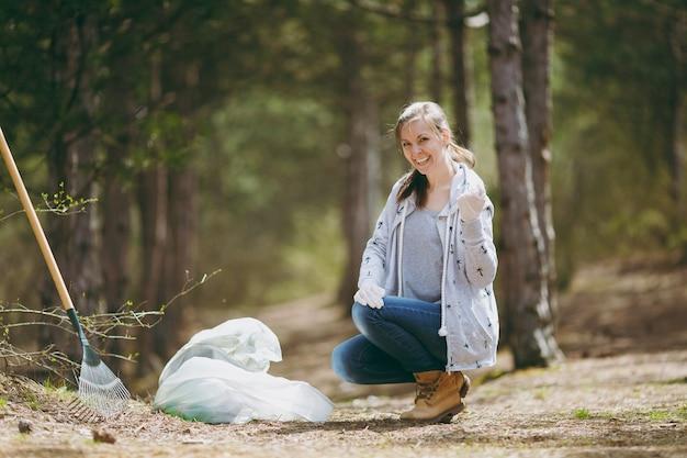 Молодая улыбающаяся женщина убирает мусор в мешки для мусора и показывает кулак в парке или лесу