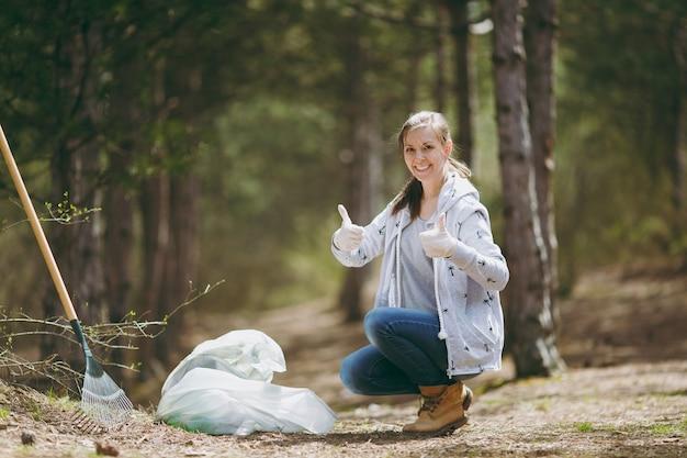 Молодая улыбающаяся женщина убирает мусор в мешки для мусора, показывает палец вверх в парке или лесу