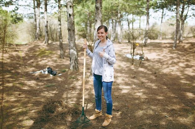 쓰레기 수거를 위해 갈퀴를 사용하여 청소하고 흩어져 있는 공원에서 엄지손가락을 보여주는 젊은 웃는 여자. 환경오염 문제
