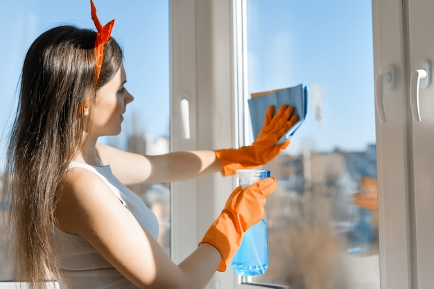 Young smiling woman cleaning window