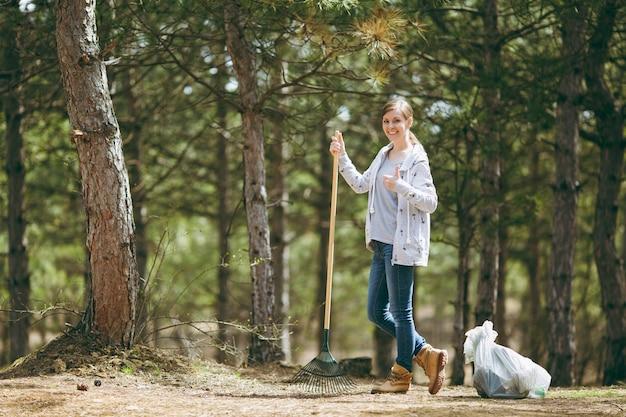 쓰레기 수거를 위해 갈퀴로 청소하고 공원의 쓰레기 봉투 근처에 엄지손가락을 보여주는 젊은 웃는 여자. 환경오염 문제