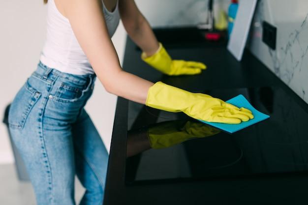 若い笑顔の女性は彼女の家の台所を掃除します