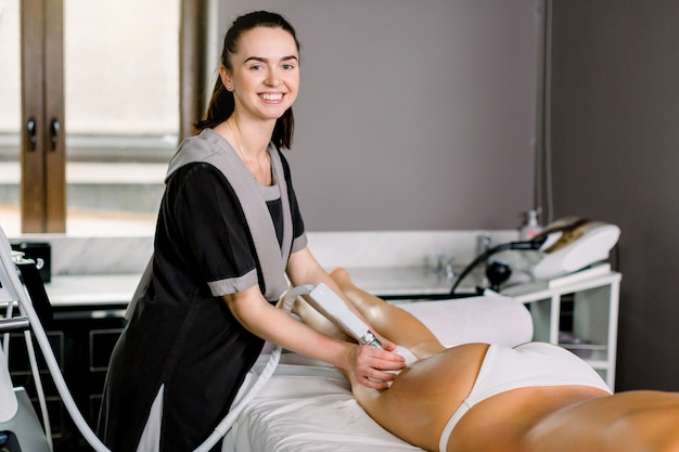 Young smiling woman cosmetologist with roller doing buttocks massage for her female client in modern spa medical center.