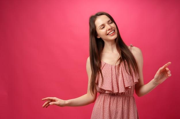 Молодая улыбающаяся женщина танцует с раскинутыми руками на розовом фоне