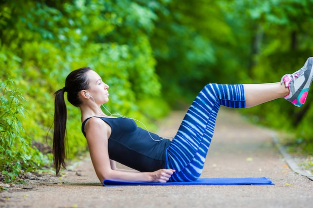 Young smiling woman doing sporty exercises outdoors