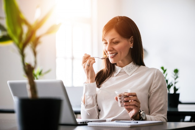 Young smiling woman eating ice cream in office