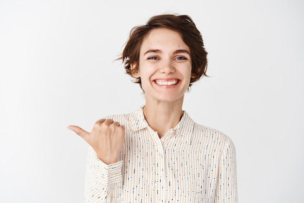 Young smiling woman employee looking happy and proud, pointing finger left company, standing against white wall