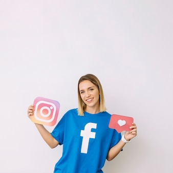 Young smiling woman in facebook t-shirt holding instagram and like icon