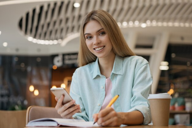 携帯電話を使用して、トーンを取り、カフェで働く若い笑顔の女性フリーランサー