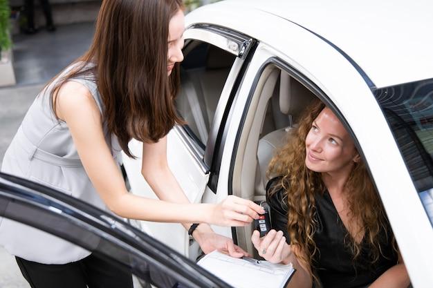 Молодая усмехаясь женщина получая ключ нового автомобиля.
