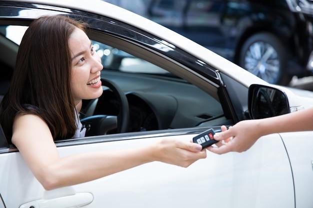 新しい車のキーを得る若い笑顔の女性。