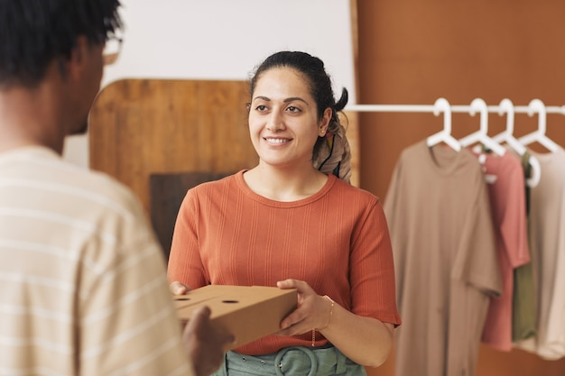 Young smiling woman giving the packed parcel to delivery man they working in delivery service