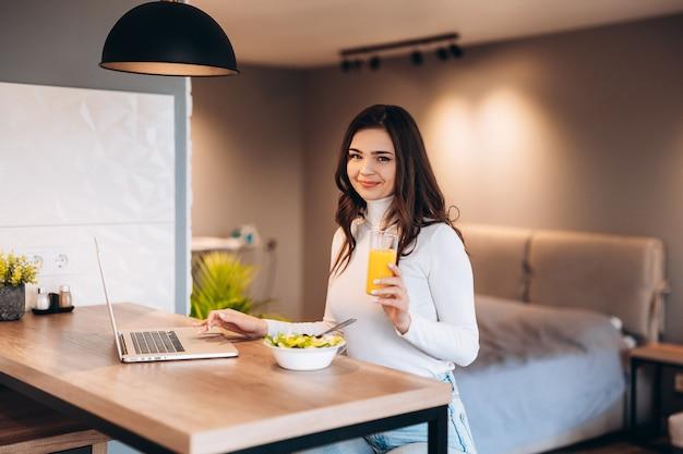 キッチンで朝食をとっている若い笑顔の女性は、ラップトップに接続し、健康的なオレンジジュースを飲んでいます。屋内でフリーランス。