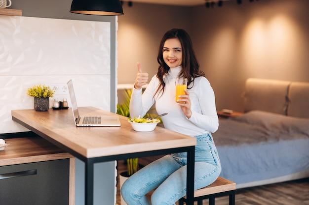 キッチンで朝食をとっている若い笑顔の女性は、ラップトップに接続し、健康的なオレンジジュースを飲んでいます。