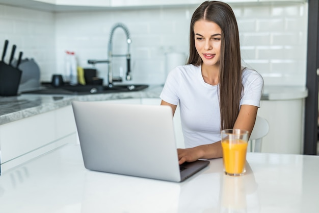 Young smiling woman having breakfast in the kitchen connecting with a laptop and drinking an healthy orange juice