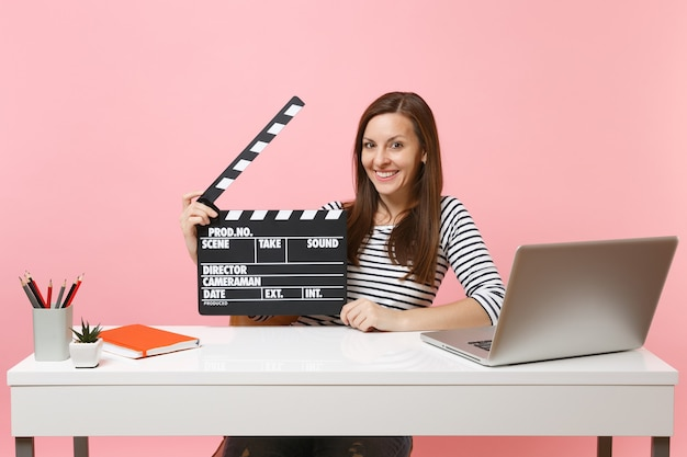 La giovane donna sorridente tiene il classico film nero che fa il ciak lavorando sul progetto mentre si siede in ufficio con il laptop