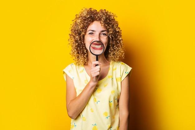 노란색 표면에 돋보기를 들고 젊은 웃는 여자