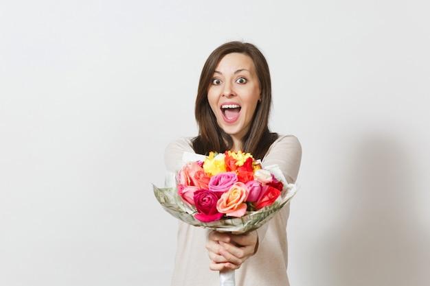 흰색 배경에 고립 된 아름 다운 장미 꽃의 꽃다발을 들고 젊은 웃는 여자. 광고 공간을 복사합니다. 텍스트에 대 한 장소. 성 발렌타인 데이 또는 국제 여성의 날 개념