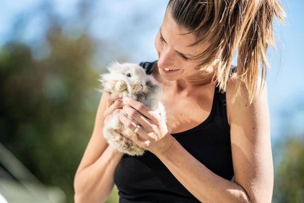Молодая улыбающаяся женщина, держащая пушистого кролика в руках на улице в солнечный день.