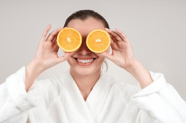 彼女の目の前で彼女の手に半分のオレンジを保持している若い笑顔の女性