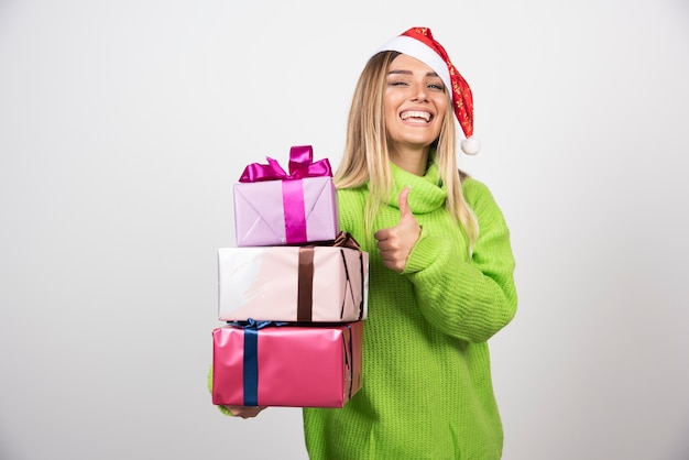 Young smiling woman holding in hands festive christmas presents.