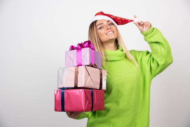 Giovane donna sorridente che tiene in mano i regali di natale festivi
