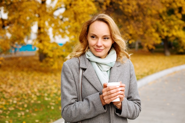 Young smiling woman holding hot cup of coffee warming hands and looking into the distance