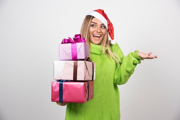 お祝いのクリスマスプレゼントを手に持って若い笑顔の女性