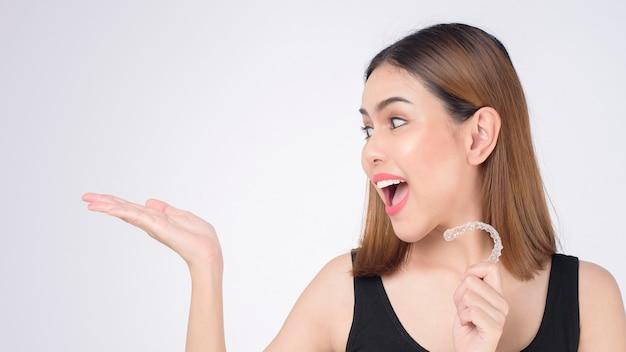 스튜디오, 치과 의료 및 교정 개념에서 invisalign 교정기를 들고 웃는 젊은 여성