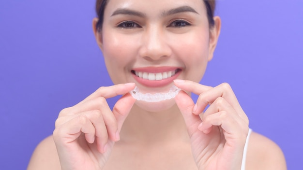 A young smiling woman holding invisalign braces in studio, dental healthcare and orthodontic concept.