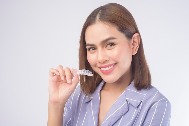 A young smiling woman holding invisalign braces on white