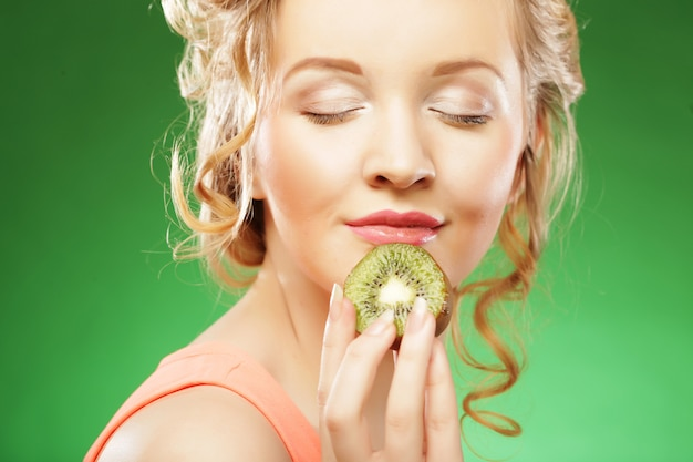 Young smiling woman holding kiwi