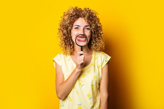 Young smiling woman holding a magnifying glass on a yellow surface