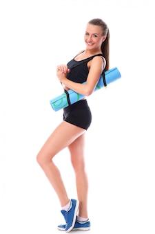 Молодая усмехаясь женщина держа циновку для фитнеса