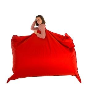彼女の肩に保持している若い笑顔の女性リビングルームまたは白で隔離された他の部屋のための赤い長方形のビーンバッグソファチェア