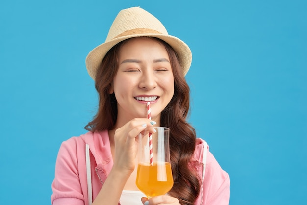 オレンジジュースのガラスを保持している若い笑顔の女性。ビタミン飲料の女の子。
