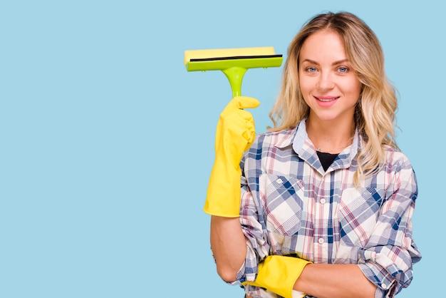 Молодая усмехаясь женщина держа пластичный счищатель смотря камеру против голубой предпосылки