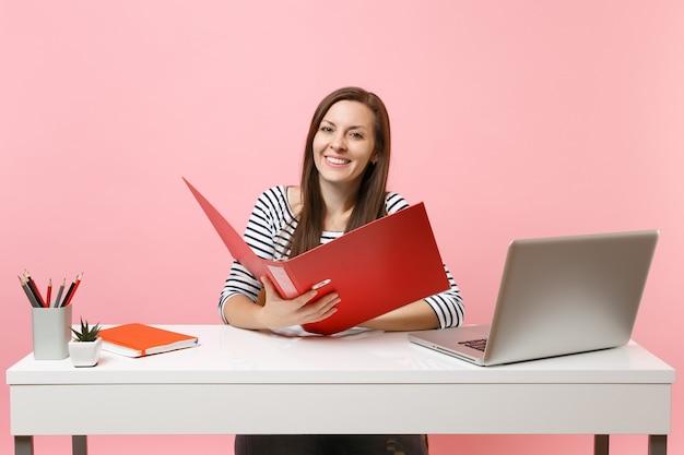 Молодая улыбающаяся женщина, держащая красную папку с бумажными документами, работающая над проектом, сидя в офисе с ноутбуком