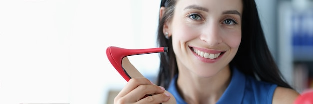 Young smiling woman holding red highheeled sandals in hands