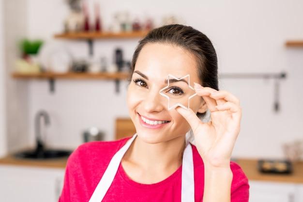 あなたを見ながら彼女の目で自家製クッキーの星型カッターを保持している若い笑顔の女性