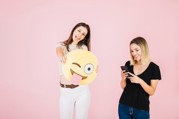 Young smiling woman holding winking eye emoji near her friend using cellphone
