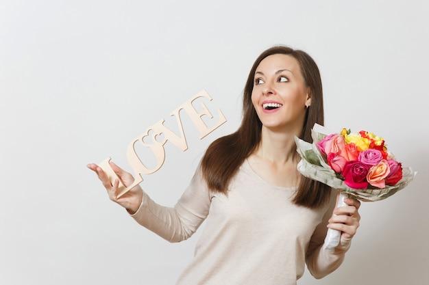 나무 단어 사랑, 흰색 배경에 고립 된 아름 다운 장미 꽃의 꽃다발을 들고 젊은 웃는 여자. 광고 공간을 복사합니다. 성 발렌타인 데이 또는 국제 여성의 날 개념.